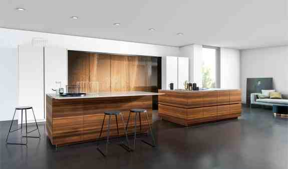 eggersmann MOTION sliding countertops close to hide an induction cooktop and stow away a massive breakfast table