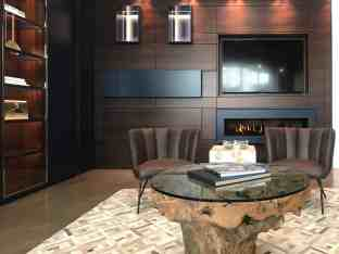 modern dark cabinetry, luxury custom furniture, and organic textures create a warm, inviting flexible study or living room space