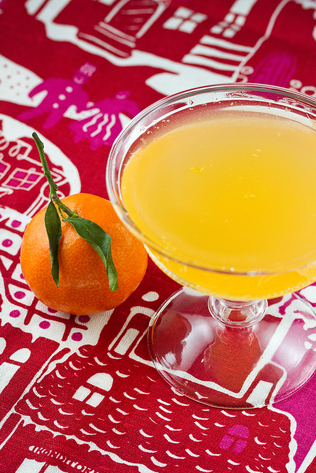 A glass of quince vodka with clementine juice and prosecco