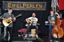 """Musiker Uwe Reetz (Mitte) stimmt das Publikum mit seinen """"Eifelperlen"""" im Foyer der Tonfabrik auf den Musikmarathon in der Diskothek ein. (Foto: Reiner Züll)"""