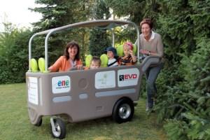 """Herta Weiss von der Energie Nordeifel (links) und Tagesmutter Petra Gemünd (rechts) stellten mit den Kindern den neuen Krippenwagen für das """"Spatzennest"""" vor. Bild: Michael Thalken/Eifeler Presse Agentur/epa"""