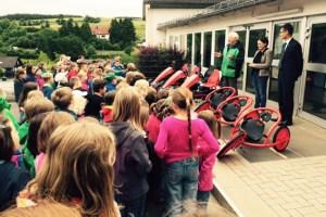 Heinz Hentz (v.l.), Mirjam Schmitz und Jan Lembach übergaben die neuen Fahrzeuge an die Grundschulkinder. Bild: Gemeinde Dahlem