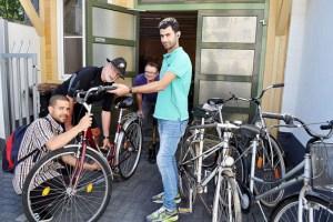 Bounadja Qaddouz (v.l.), Karl-Heinz Arimond, Peter Müller-Gewiss (Caritas) und Mohamed Mohamed in der Fahrradwerkstatt. Bild: Carsten Düppengießer