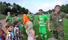 Organisator und Moderator Andreas Duwe (rechts) mit den Kindern, die mit den Spielern auf den Rasen aufliefen. Foto: Reiner Züll