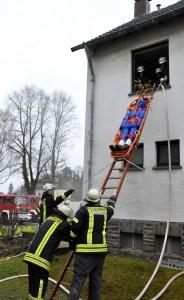 """Mit Hilfe einer Schelifkorbtrage wird ein """"Verletzter"""" aus dem ersten  Obergeschoss über eine Steckleiter abgeseilt. Foto: Reiner Züll"""