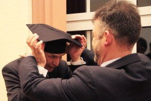 Für sein großes Engagement erhielt Bürgermeister Udo Meister von Professor Dr. Alexander Polack spaßeshalber ebenfalls einen Doktorhut. Bild: Michael Thalken/Eifeler Presse Agentur/epa