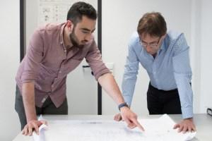 Mohamad Hasan Dakkak (links), heute als Ingenieur in Monschau tätig, bespricht mit Geschäftsführer Kurt Heinen die einzelnen Produktionsschritte eines neuen Auftrags. Bild: Dagmar Grömping/Jobcenter EU
