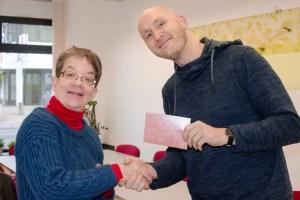 Sabine Renner, ausgebildete Qigong-Lehrerin, übergab die Spenden an Arndt Krömer, dem Pressesprecher der Caritas Schleiden. Bild: Caritas