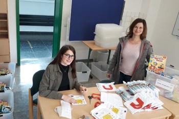 Beim Packen der Sprachförderboxen: SmiLe-Koordinatorin Suzana Kilickeser (rechts) mit Praktikantin Daniela Poth. Foto: KoBIZ