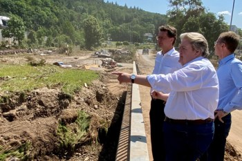 Klaus Voussem (vorne) zeigte Verkehrsminister Wüst die Schäden in Iversheim, rechts im Bild Detlef Seif (MdB). Bild: David Dreimüller