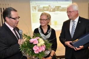 Als Wahlleiter übergab der Erste Beigeordnete Uwe Schmitz (links) dem Bürgermeister Papstwein und Edith Radermacher einen großen Blumenstrauß. Bild: Reiner Züll
