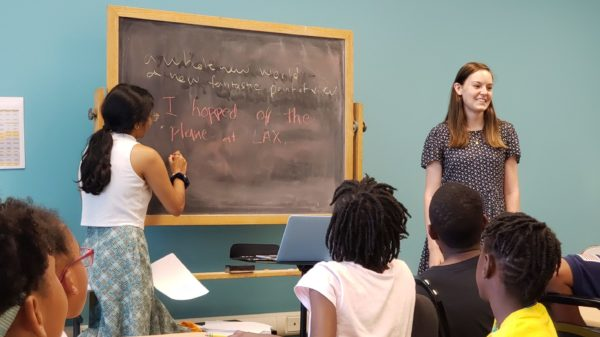 826DC interns stand in front of a chalkboard as students look on.