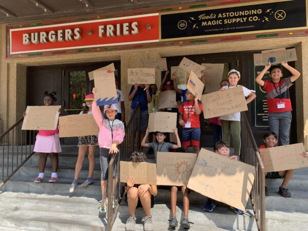 826DC students hold up environmental protest signs.