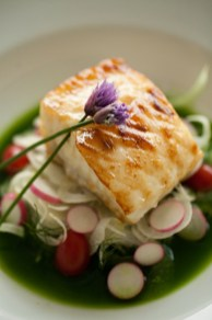 Cod with chive blossoms over green sauce