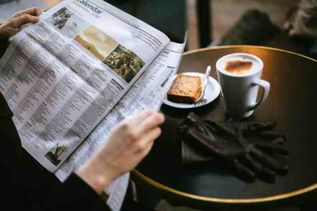 A person reading a newspaper at a coffee shop.