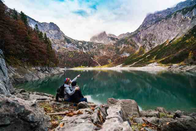 A couple surrounded by mountains and a lake.