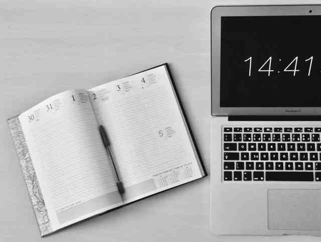 A laptop and time management planner.