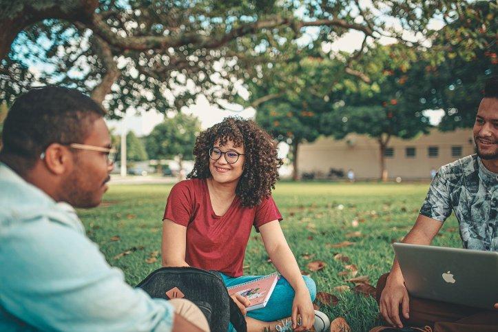 3人の学生たちが芝生の上に座り、楽しそうに会話している - 函館英会話教室EigoLa