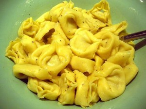 A pile of plain tortellini on a green plate.