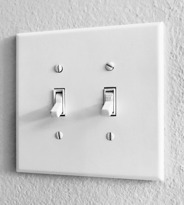 Light switch wall plate with two switches. Most of us reach for switches by habit when we enter a room.