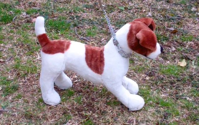 stuffed dog wearing prong collar getting leash corrections