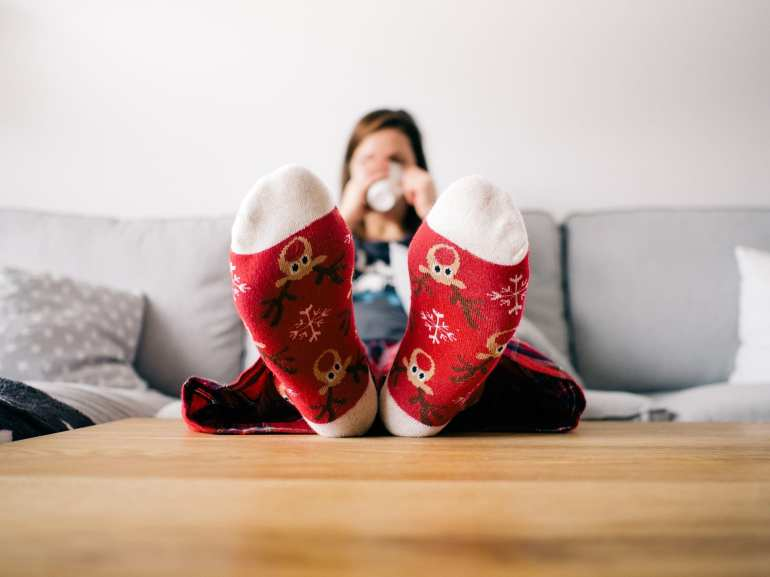 Reindeer socks in foreground, feet up of woman drinking hot drink on sofa