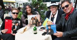 Falco, Thomas Anders, Frank Zander und Nino de Angelo an einem Tisch auf dem Hallenplan.