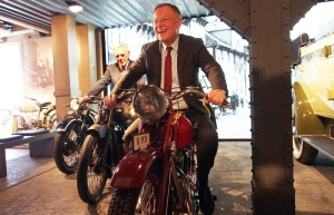 """War fasziniert von der Ausstellung im PS-Speicher: Ministerpräsident Stephan Weil, """"verfolgt"""" auf dem Motorrad von Karl-Heinz Rehkopf."""