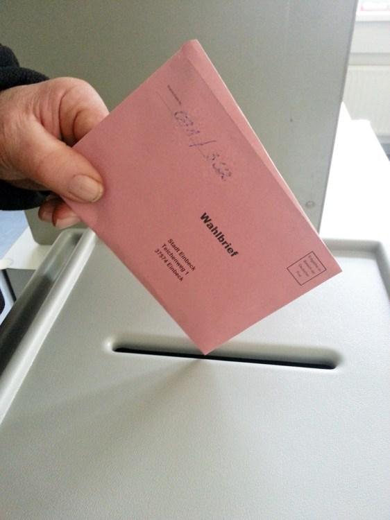 Die Briefwahl ist eröffnet, die ersten roten Umschläge mit den ausgefüllten Stimmzetteln liegen in der Urne.