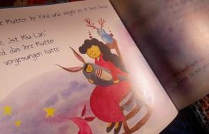 Miu Lans Mutter wie sie das Kind in einem schaukelstuhl wiegt und singt, auf der lehne sitzt eine blaue Eule mit Hirschgeweih, zu ihren Füßen ein rosa Fuchs.