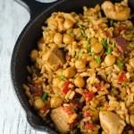 Reis mit Hähnchen, Chorizo und Kichererbsen in einer gusseisernen Pfanne von oben fotografiert