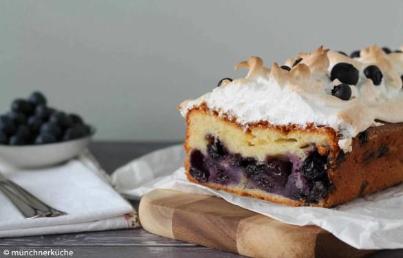 Anschnitt eines Heidelbeer-Quark-Kuchens mit Baiserhaube von vorne fotografiert