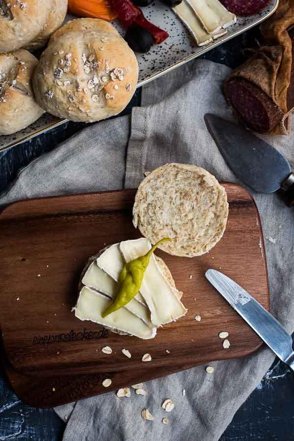 Milchbrötchen mit Haferflocken auf einem Holzbrett auf dem Frühstückstisch von oben fotografiert
