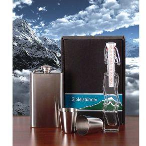 Flachmann und zwei Schnapspinchen aus rostfreiem Stahl, sowie 40 ml Obstbrand 38 % vol.in geschwungener Bügelverschluss-Flasche, in schwarzem Geschenkkarton. Maße: ca. L16,8 x B10,9 x H3,3 cm.<br>
