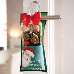 Der Türhänger ist gefüllt mit 125g feinster Schoko-Adventsmischung, bestehend aus Pralinen, Domino-Steinen, Lebkuchen, Keksen und Marzipanspezialitäten. Die Vorderseite des Türhängers ist bedruckt mit einem zwinkernden Weihnachtsmann und dem Spruch Bitte schnell wegputzen, auf der Rückseite zwinkert das liebevolle Rentier mit dem Hinweis Bitte nicht stören ich nasche, Maße: ca. H28,5 x B11,5 cm. Zutaten: WEIZENMEHL, Zucker, Bienenhonig, Kakaomasse, Kakaobutter,VOLLMILCHPULVER, MANDELN, HASELNÜSSE, Kakaopulver, Orangeat, VOLLEI, Johannisbeeren, Pflaumen, Vanille, Gewürze, Emulgator: SOJALECITHIN, Geliermittel: PEKTINE; Backtriebmittel: Ammoniumcarbonat, Farbstoffe: Beta Carotin, Karmin, Patentblau. Nährwertangaben: Energie 1604 kJ (383 kcal); Fett: 15,80g, davon ges. Fettsäuren 10,40g; Kohlenhydrate 46,30g, davon Zucker 29,40g; Eiweiß 3,20g; Salz 0,15g. Allergiehinweis: Kann Spuren von anderen Schalenfrüchten enthalten<br>