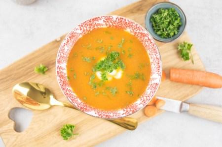 Türkische rote Linsen Suppe von oben fotografiert. Die Suppe ist mit frischem Naturjoghurt und mit fein gehackter Petersilie angerichtet.