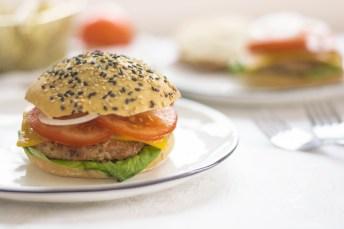 Jackfrucht Burger von vorne fotografiert. Der Burger liegt auf einem weißen Teller. Neben dem Teller liegen zwei Gabeln.
