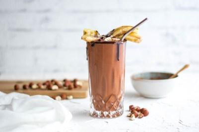 Auf diesem Bild ist eine zuckerfreie und vegane Bananen - Kakaomilch zu sehen. Die Bananen - Kakaomilch wurde in ein schönes Glas gefüllt auf dem gebratenen Bananen, Haselnüsse und Schokolade zu sehen sind. Im Hintergrund ist eine Schüssel mit Kakaopulver und ein Brett, auf dem Haselnüsse liegen.