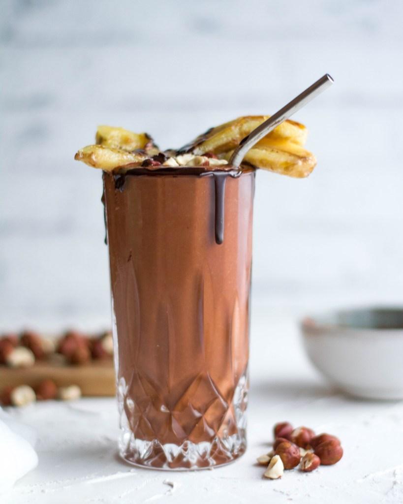 Hier ist eine zuckerfreie und vegane Bananen - Kakaomilch zu sehen. Der Kakao wurde in einem eleganten Glas angerichtet mit einem Metall - Strohhalm. Im Hintergrund liegen Haselnüsse und man kann eine Schale mit Kakaopulver sehen.