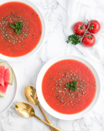 Diese warme Wassermelonensuppe wurde in weißen Schüsseln angerichtet und mit Kräutern dekoriert. Daneben liegen zwei goldene Löffel und frische Tomaten und Wassermelonen Stücke.