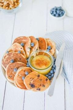 Zuckerfreie Heidelbeer Pancakes von oben fotografiert. Zwischen den Heidelbeer Pancakes steht eine Schüssel mit Apfelmus.