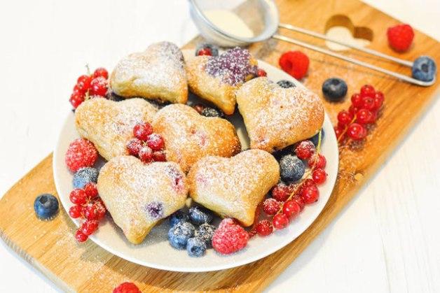 Auf diesem Bild sind zuckerfreie Beerenmuffins zu sehen. Die Beerenmuffins wurden in Herzform gebacken.