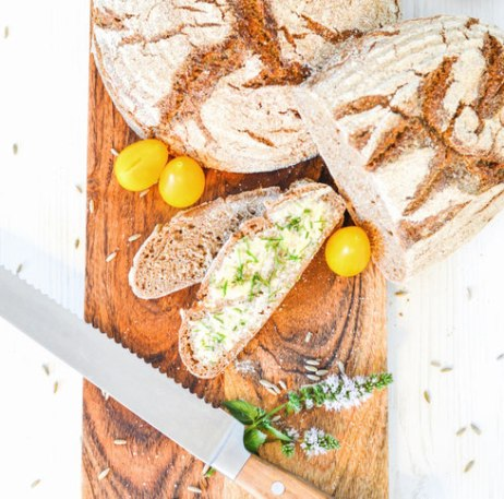 Das Vollkornbrot mit Sauerteig liegt auf einem geölten Holzbrett. Davor liegt ein Brotmesser und eine Brotscheibe ist mit Butter bestrichen. Auf der Butter liegt frischer Schnittlauch.