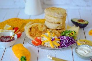 Auf diesem Bild sind Dinkel Frühstücks - Toasties zu sehen. Sie wurden übereinander gestapelt und daneben liegt jede Menge frisch geschnittenes Gemüse.