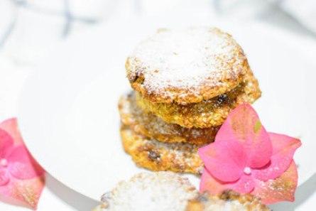 Zuckerfreie Erdmandel Kekse auf einem weißen Dessertteller. Im Hintergrund sieht man eine rosa Blüte und ein Geschirrtuch.