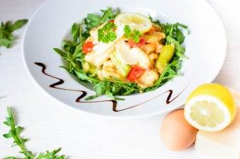 Auf diesem Bild sind Gnocchi mit grünem Spargel und Kirschtomaten zu sehen. Das Bild wurde von oben fotografiert und daneben liegt eine Zitrone und Rucola.