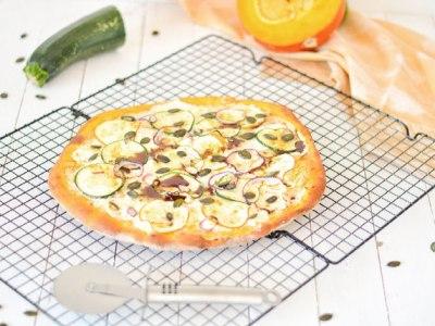 Auf diesem Bild ist eine Kürbispizza mit Zucchini und Feta zu sehen. Die Pizza liegt auf einem Backgitter zum Abkühlen und im Hintergrund liegt ein oranges Geschirrtuch.