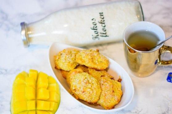 Zuckerfreie Mango - Kokos Kekse in einer weißen Schüssel. Daneben steht eine Tasse Tee.