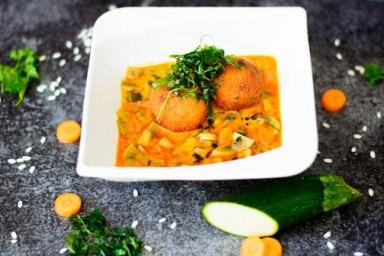Auf diesem Bild sind frittierte Risottobällchen mit Thai Curry zu sehen. Rund um das Curry liegen die Grundzutaten dafür.