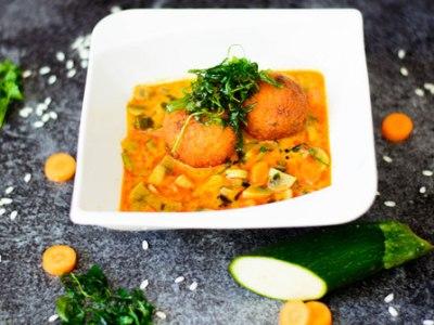Hier sind Risottobällchen auf rotem Thaicurry zu sehen. Das Curry wurde von schräg oben fotografiert. Daneben liegt viel frisches Gemüse.